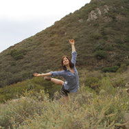 Dancer posing in middle of grassy area with a large hill in background