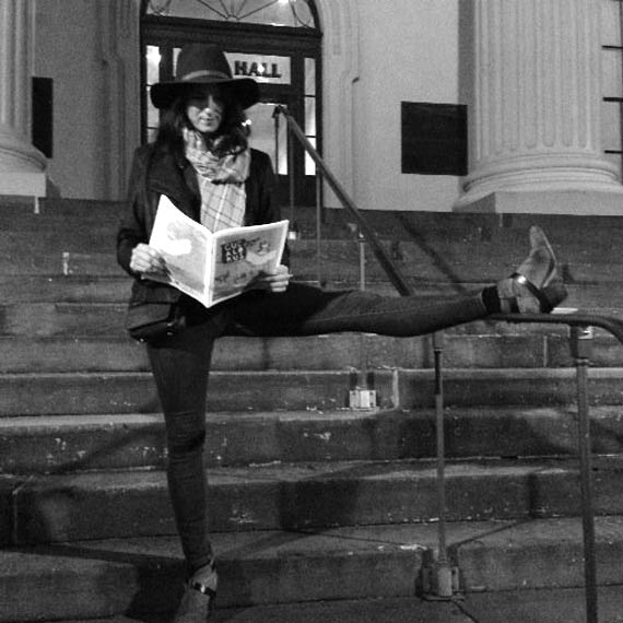 Mary John reading the newspaper in front of city hall
