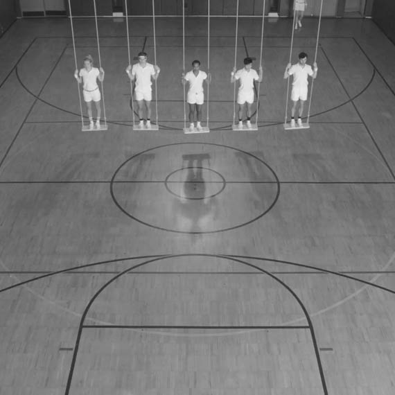 Five dancers in  white shirt and shorts on swings in gymnasiums for a Converse commercial